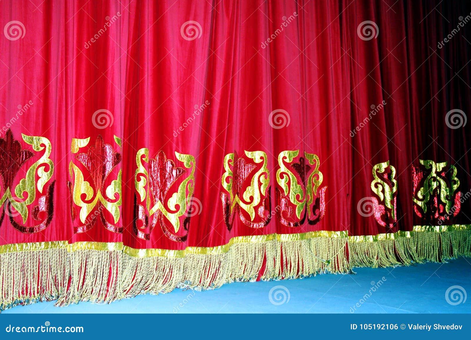 Θεατρική κόκκινη κουρτίνα βελούδου με το χρυσό υπόβαθρο σχεδίων