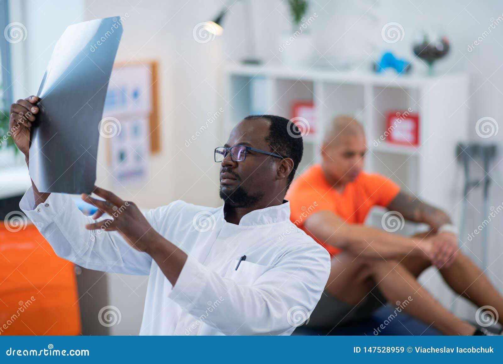 Θεράπων αφροαμερικάνων που εξετάζει την ακτίνα X προσεκτικά