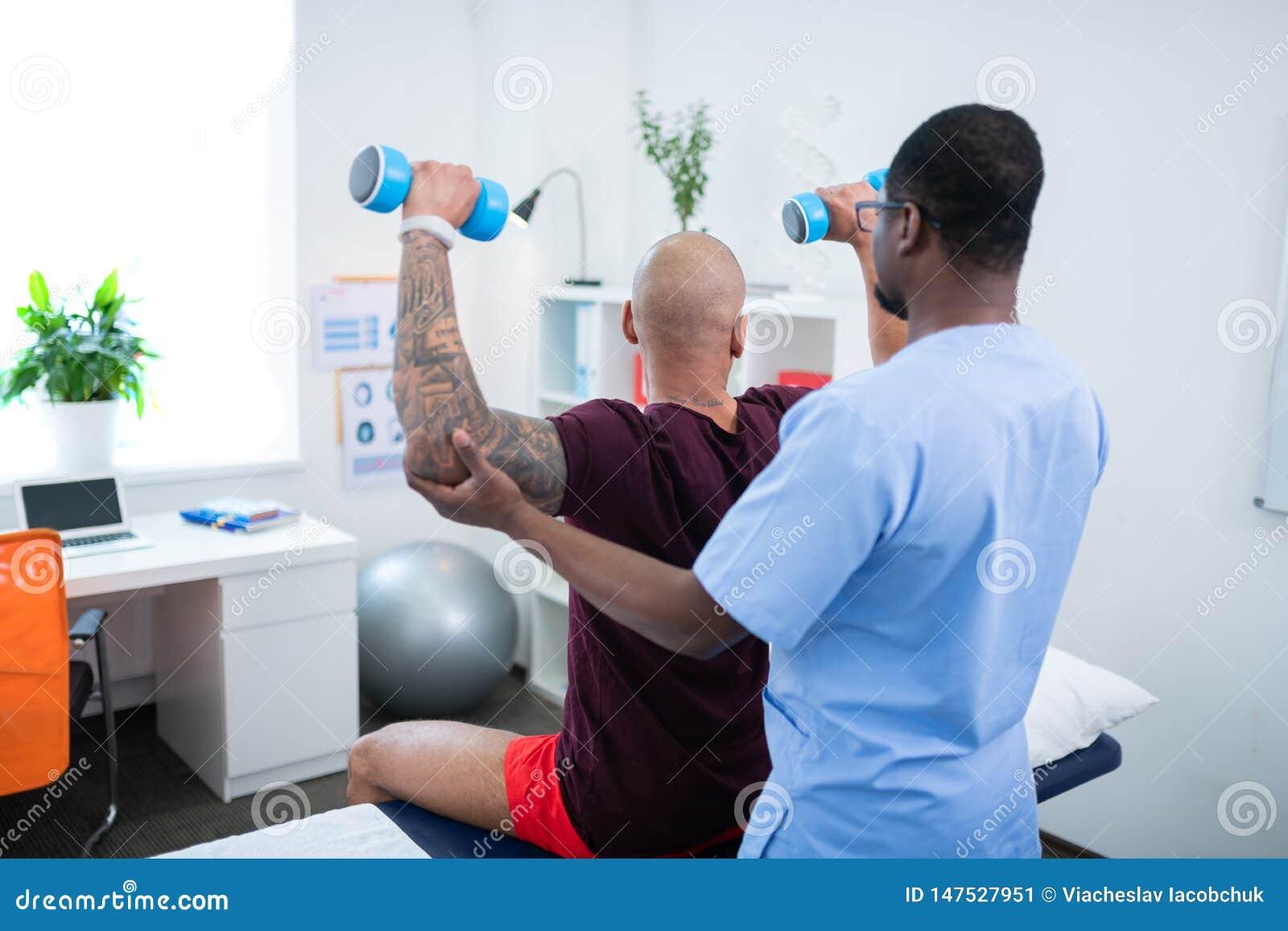 Θεράπων που βοηθά τον ασθενή του που κάνει τις ασκήσεις με τα barbells