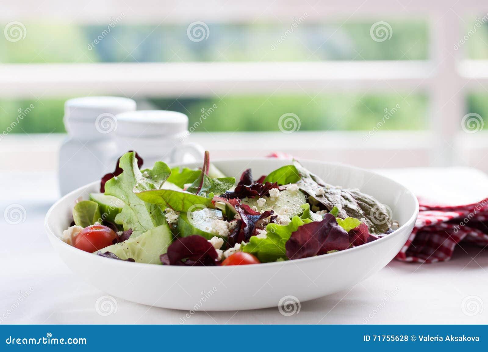 Θερινή περίοδο σαλάτα με τα φύλλα σαλάτας, τις ντομάτες, τα αγγούρια, τα ιταλικά χορτάρια και το τυρί σε ένα κύπελλο σε έναν πίνα