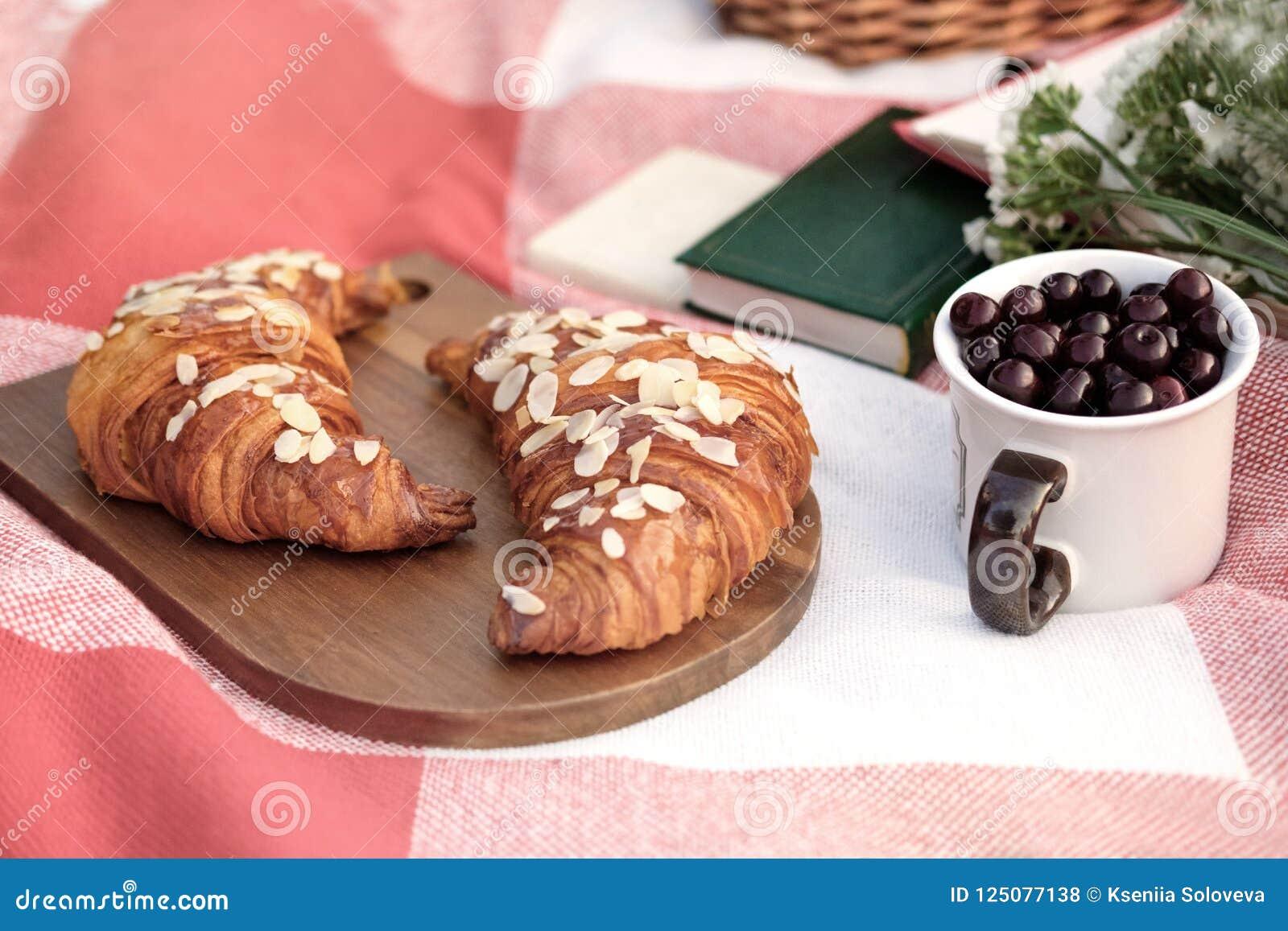Θερινό πικ-νίκ Ένα γυαλί με ένα κεράσι, δύο croissants σε έναν ξύλινο πίνακα, μια ανθοδέσμη των άσπρων λουλουδιών, βιβλία