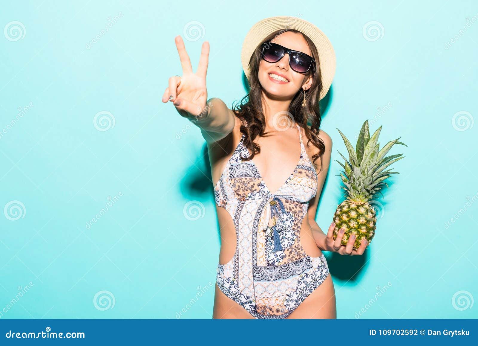 Θερινό τροπικό θετικό πορτρέτο της νέας όμορφης γυναίκας που έχει τη διασκέδαση, που φορά το φωτεινό ανανά εκμετάλλευσης μπικινιώ