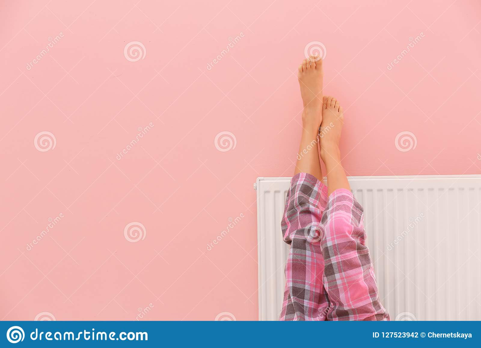 Θερμαίνοντας πόδια γυναικών στη θέρμανση του θερμαντικού σώματος κοντά στον τοίχο χρώματος, κινηματογράφηση σε πρώτο πλάνο