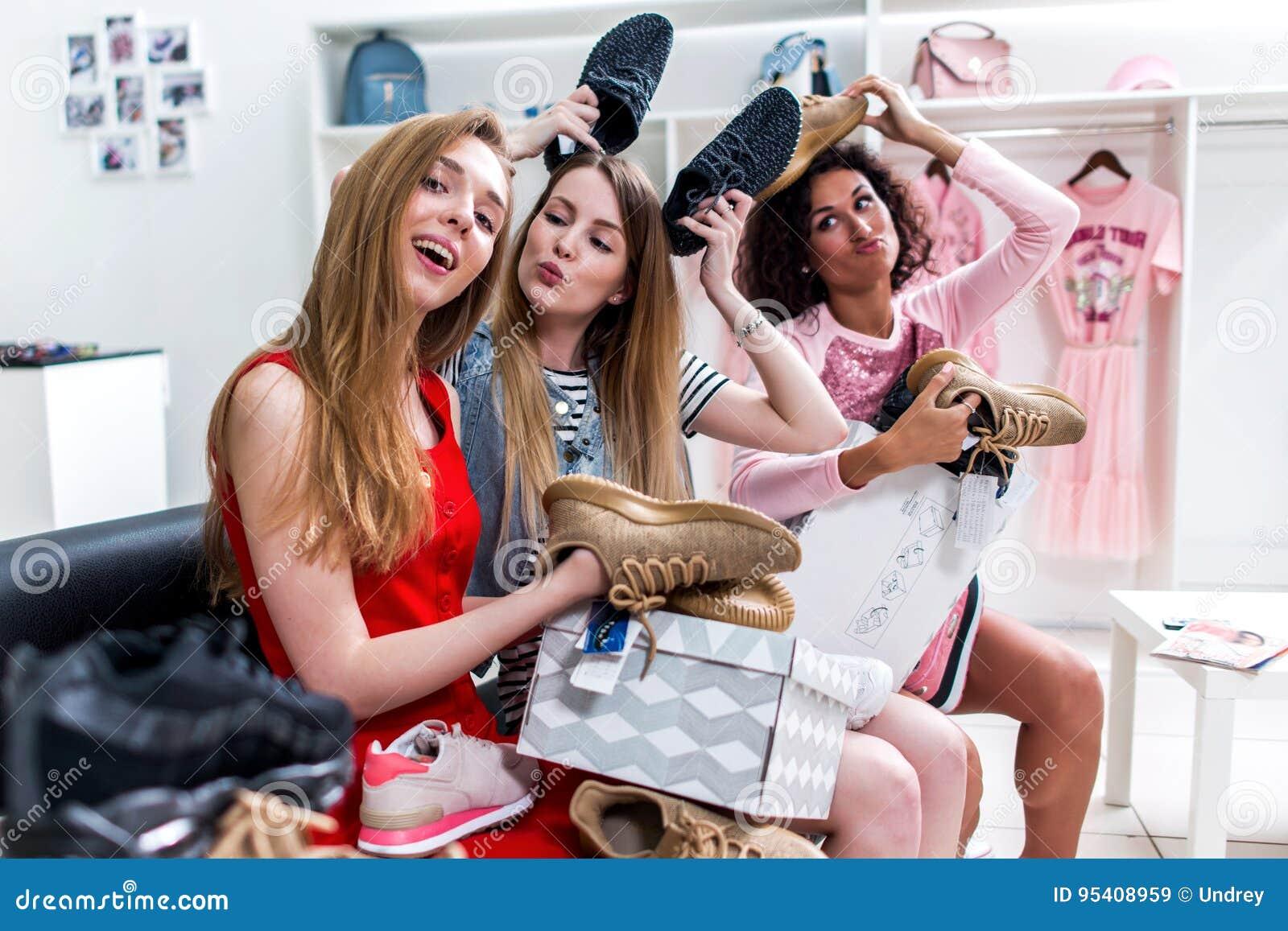 Θετικές φίλες εφήβων που έχουν το χρόνο διασκέδασης μαζί κάνοντας τη συνεδρίαση αγορών που επιλέγει νέο παπουτσιών γύρω και