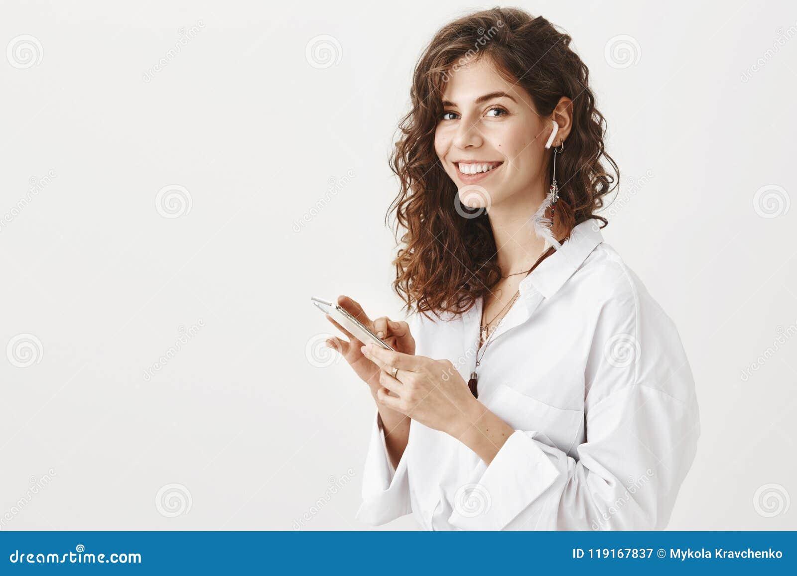 Θετική επιτυχής caucsian γυναίκα που μιλά στο smartphone μέσω των ασύρματων earbuds, που κρατούν τη συσκευή διαθέσιμη χαμογελώντα