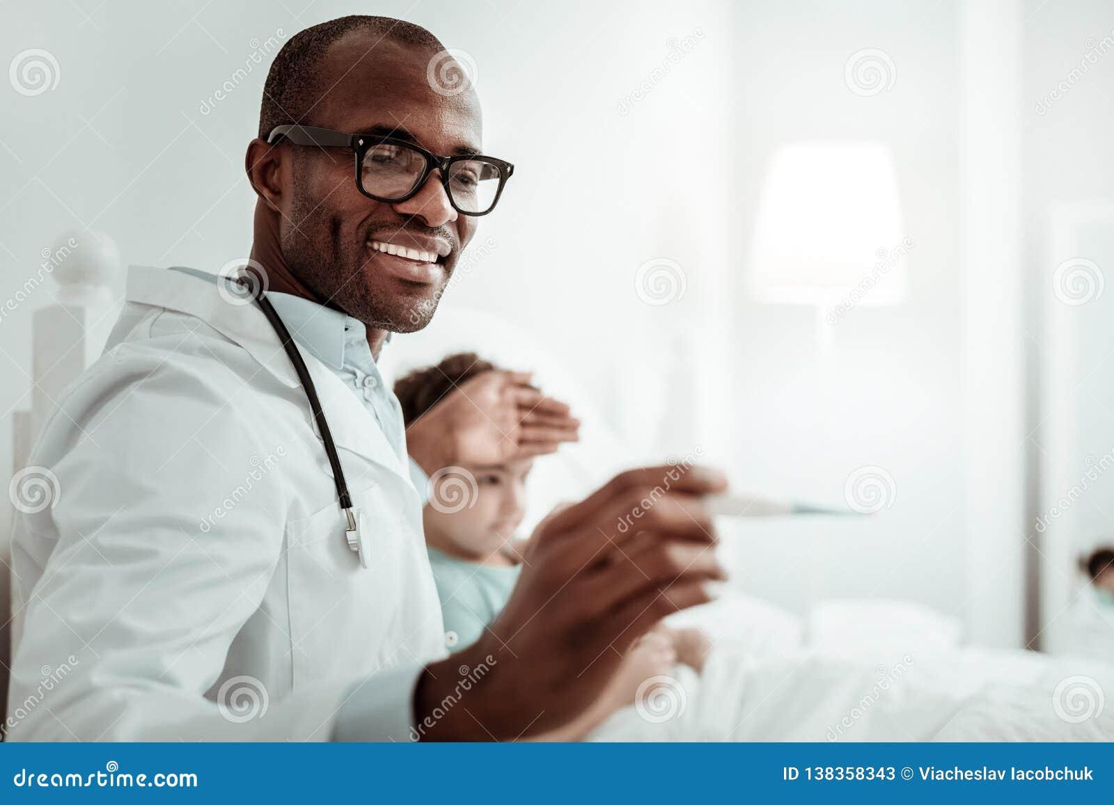 Θετικός ευχαριστημένος γιατρός που θεραπεύει τους μικρούς ασθενείς με την ευχαρίστηση