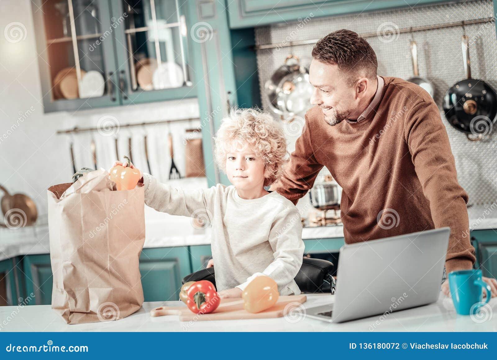 Θετικός ευχαριστημένος μπαμπάς που εξετάζει το γιο του