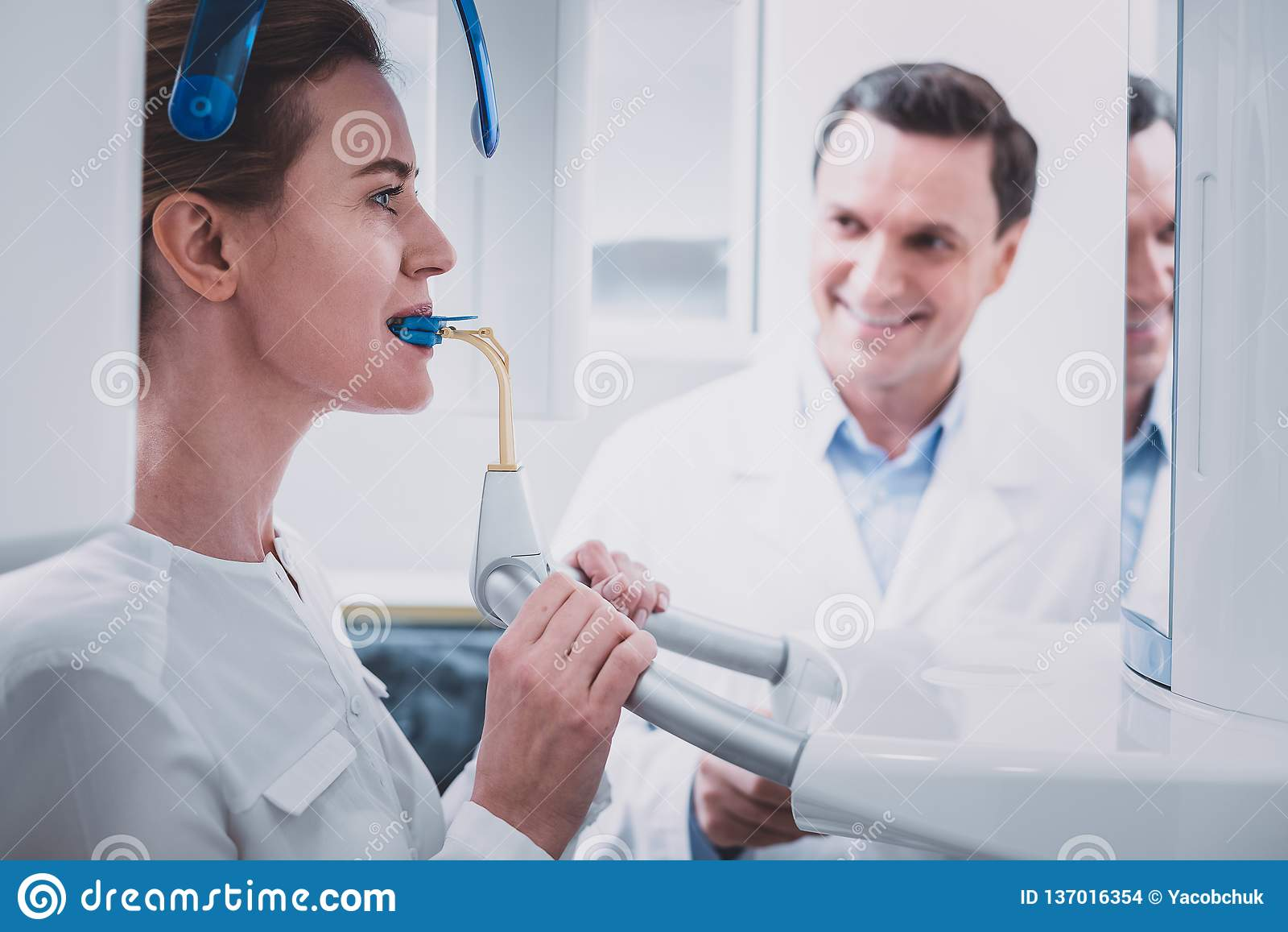 Θετικός ευχαριστημένος οδοντίατρος που εξετάζει το νέο ασθενή του
