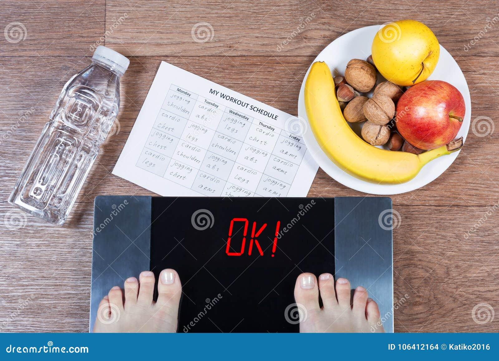 Θηλυκά πόδια στις ψηφιακές κλίμακες με τη λέξη που περιβάλλονται εντάξει από το μπουκάλι νερό, το πιάτο με τα υγιή τρόφιμα και wo