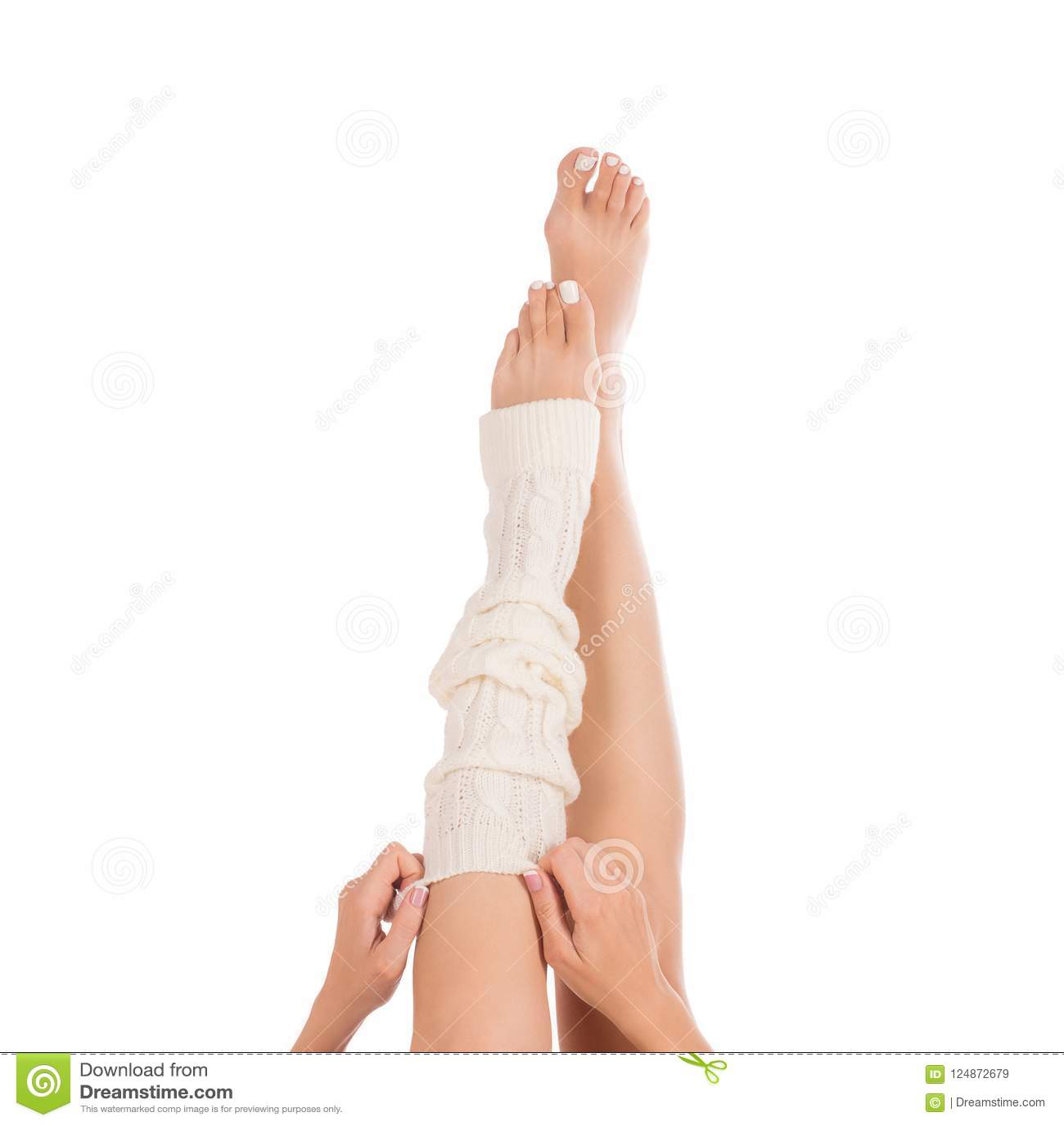 Θηλυκά πόδια στο άσπρο μαγκάλι ποδιών Θηλυκά χέρια που βάζουν σε μια περικνημίδα Άσπρο pedicure, γαλλικό μανικιούρ Κλείστε επάνω,