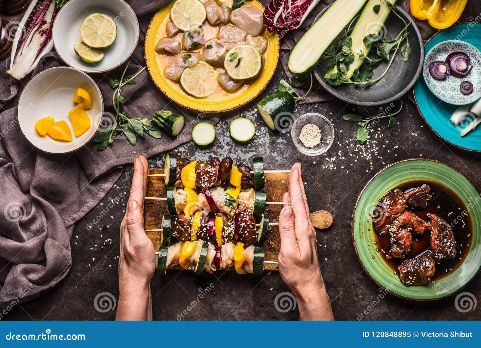 Θηλυκά χέρια που κρατούν τα διάφορα σπιτικά οβελίδια λαχανικών κρέατος για τη σχάρα ή bbq στο αγροτικό υπόβαθρο με τα συστατικά,