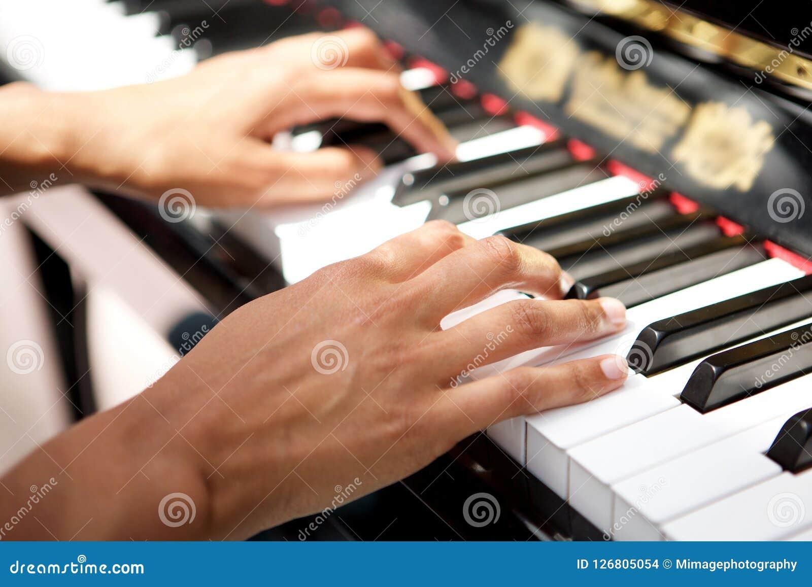 Θηλυκά χέρια που παίζουν το πιάνο