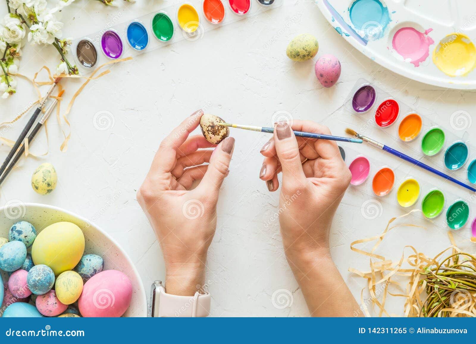 Θηλυκά χέρια που χρωματίζουν τα αυγά Πάσχας Έννοια διακοπών Επίπεδος βάλτε Τοπ όψη