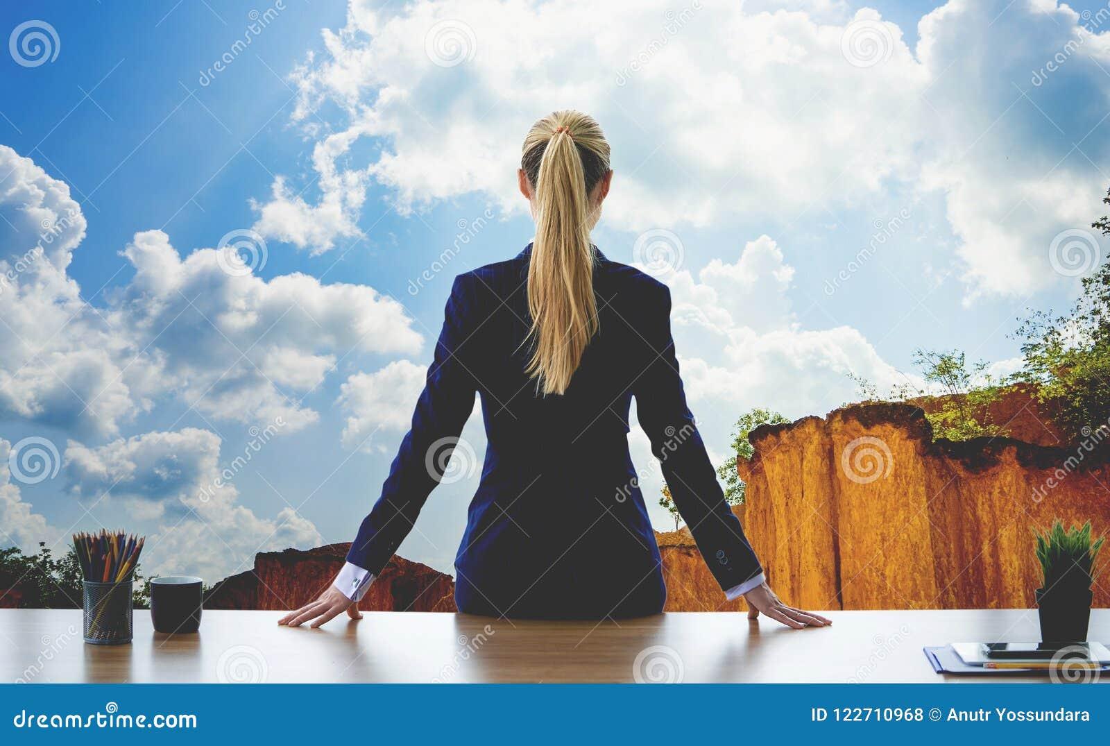 Θηλυκή επιχειρησιακή γυναίκα που φαίνεται έξω το βουνό ουρανού παραθύρων