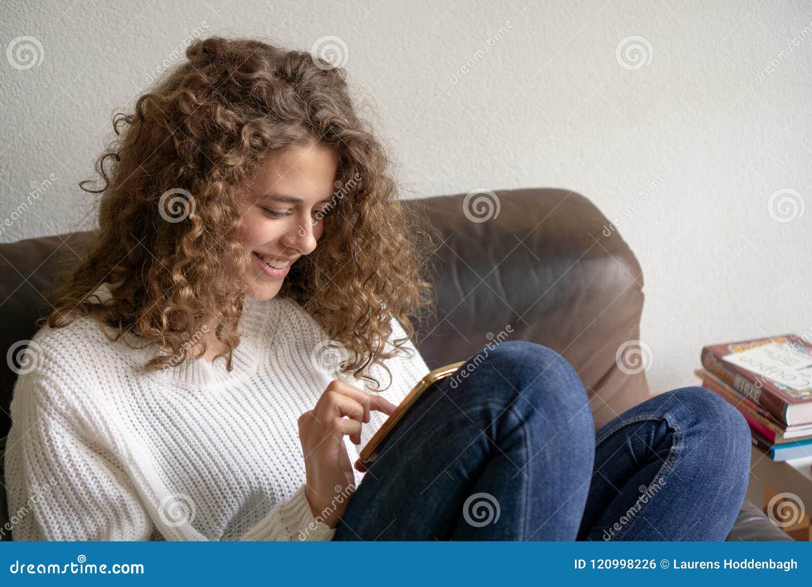 Θηλυκή συνεδρίαση εφήβων σε μια καρέκλα που είναι πολυάσχολη με το ψηφιακό π της