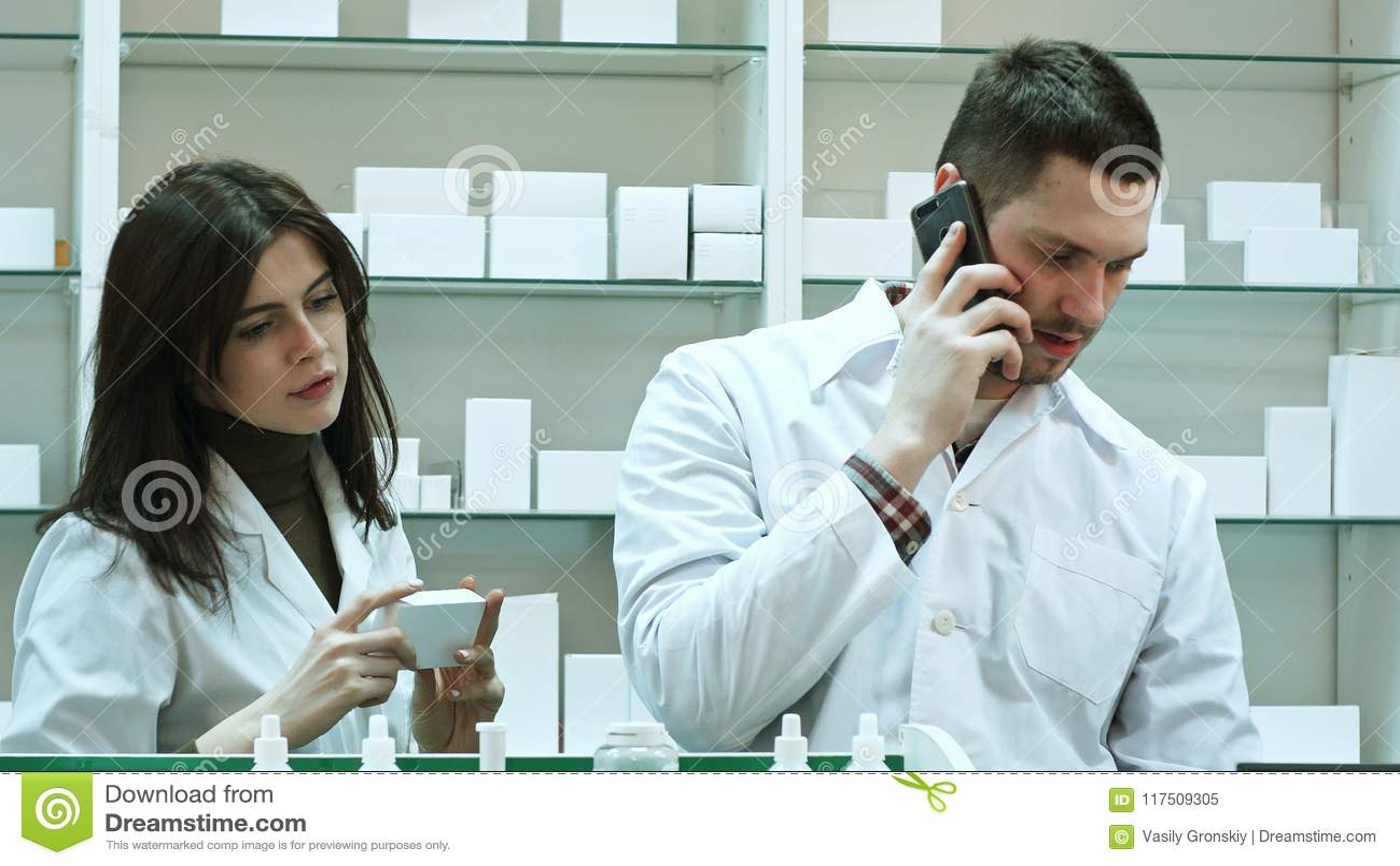 Θηλυκοί και αρσενικοί φαρμακοποιοί που εργάζονται στο φαρμακείο, που μιλούν μέσω του έξυπνου τηλεφώνου και που ελέγχουν τα χάπια