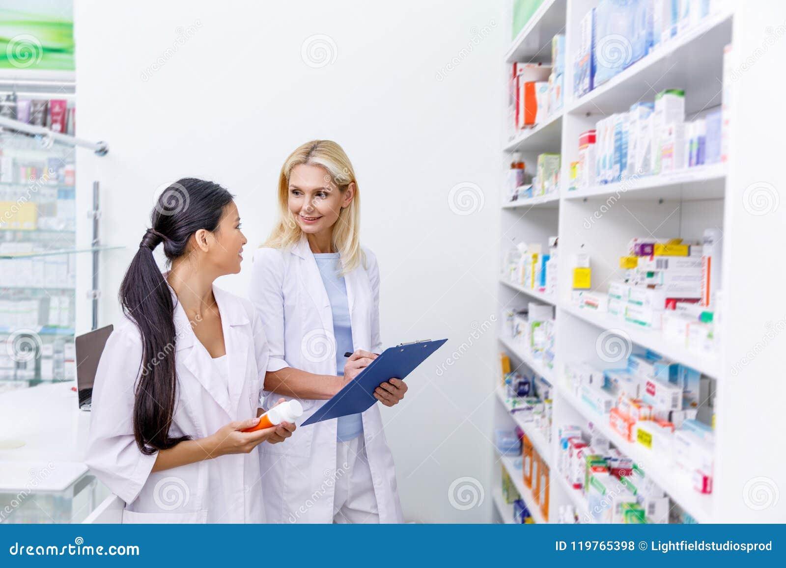 θηλυκοί φαρμακοποιοί με το φάρμακο και την περιοχή αποκομμάτων που λειτουργούν από κοινού