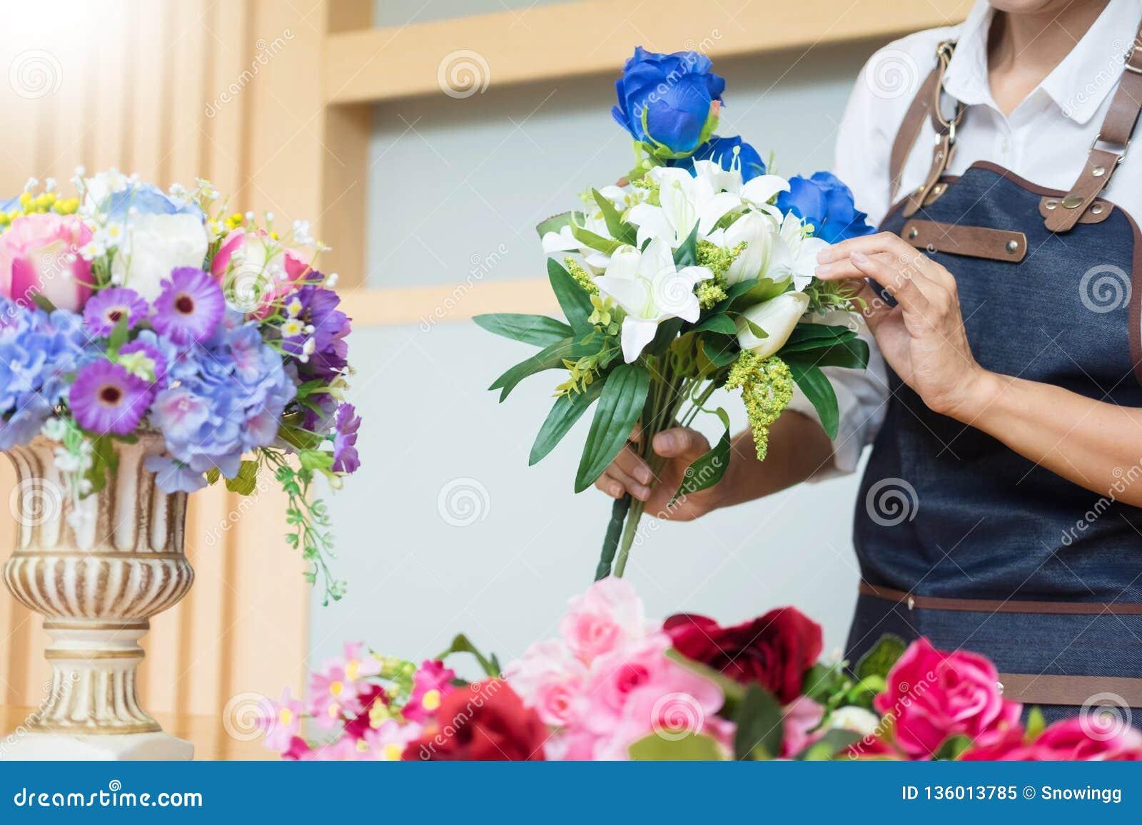 Θηλυκός ανθοκόμος στην εργασία που χρησιμοποιεί την τακτοποίηση κάνοντας την όμορφη τεχνητή ανθοδέσμη να περιβάλει στο ανθοπωλείο