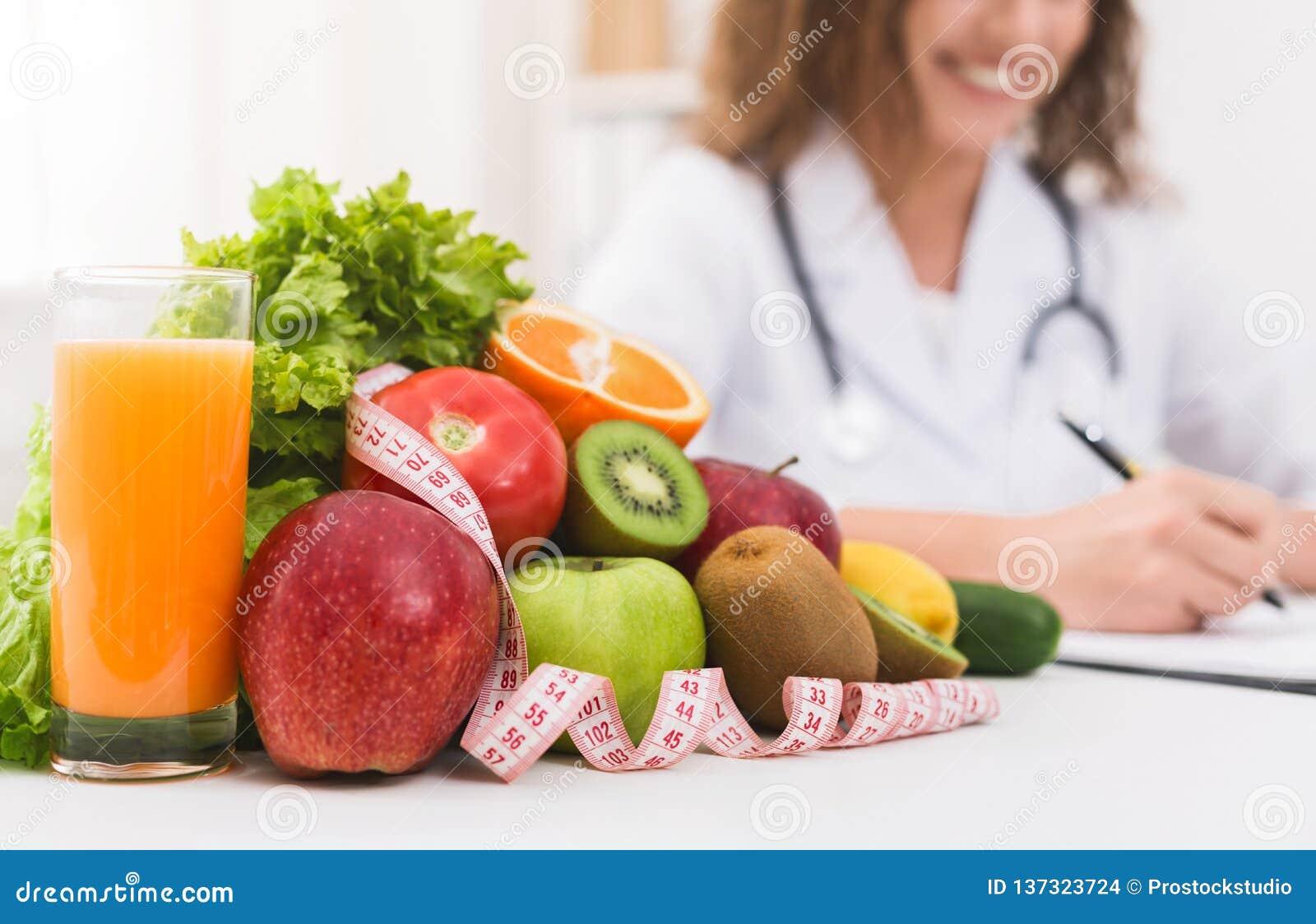 Θηλυκός γιατρός διατροφολόγων που γράφει το φυτικό σχέδιο διατροφής