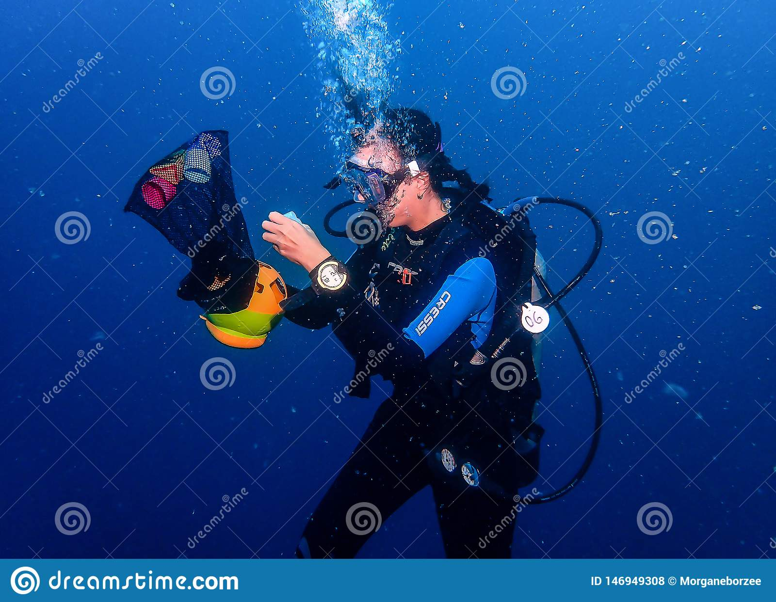 Θηλυκός δύτης σκαφάνδρων υποβρύχιος εκτελώντας μια άσκηση επιδεξιότητας