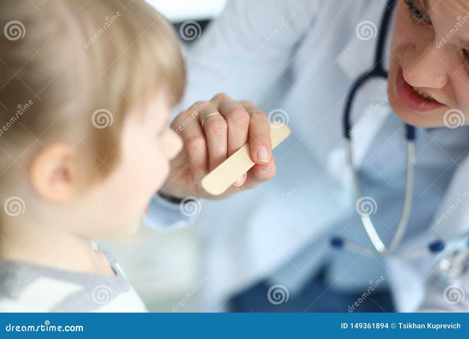 Θηλυκός παιδίατρος που εξετάζει τον υπομονετικό λαιμό παιδάκι με το ξύλινο ραβδί