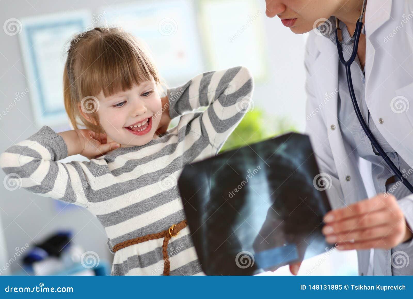 Θηλυκός παιδίατρος που συνεργάζεται με το χαριτωμένο μικρό κορίτσι στο γραφείο της που εξηγεί τη διάγνωση