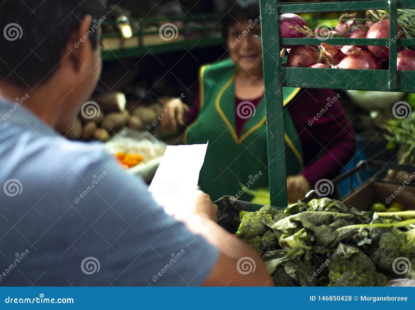 Θηλυκός περουβιανός πωλητής σε μια αγορά λαχανικών