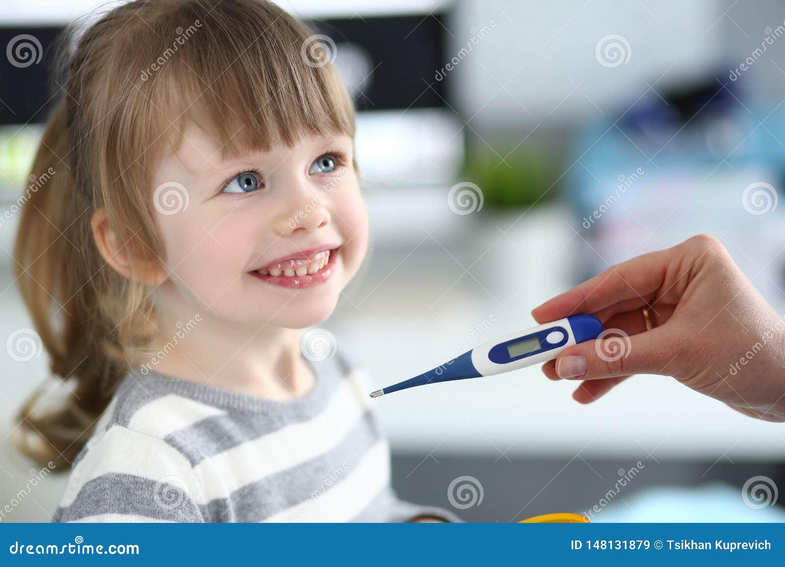 Θηλυκό θερμόμετρο εκμετάλλευσης χεριών που μετρά το άρρωστο μικρό κορίτσι