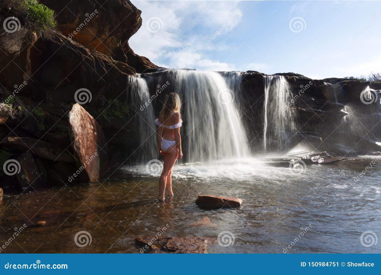 Θηλυκό που εξερευνά και που απολαμβάνει τους καταρράκτες και τις λίμνες βράχου στη φύση
