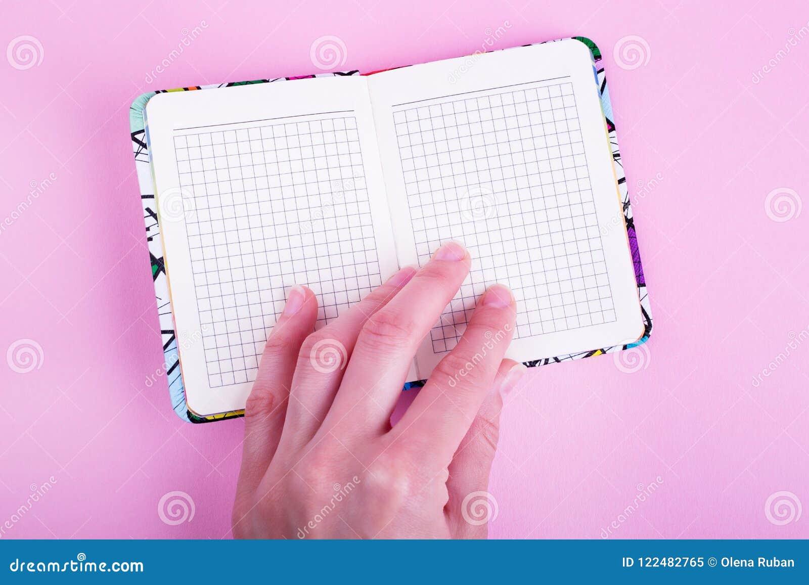 Θηλυκό χέρι και ανοικτό σημειωματάριο