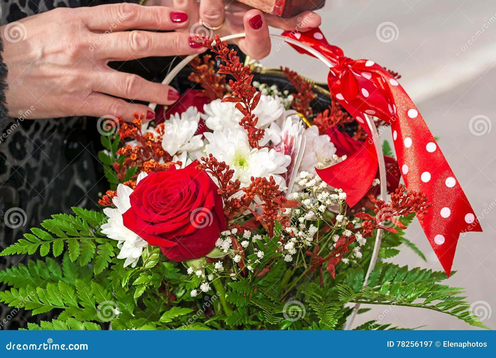 Θηλυκά χέρια που κρατούν ένα καλάθι των λουλουδιών