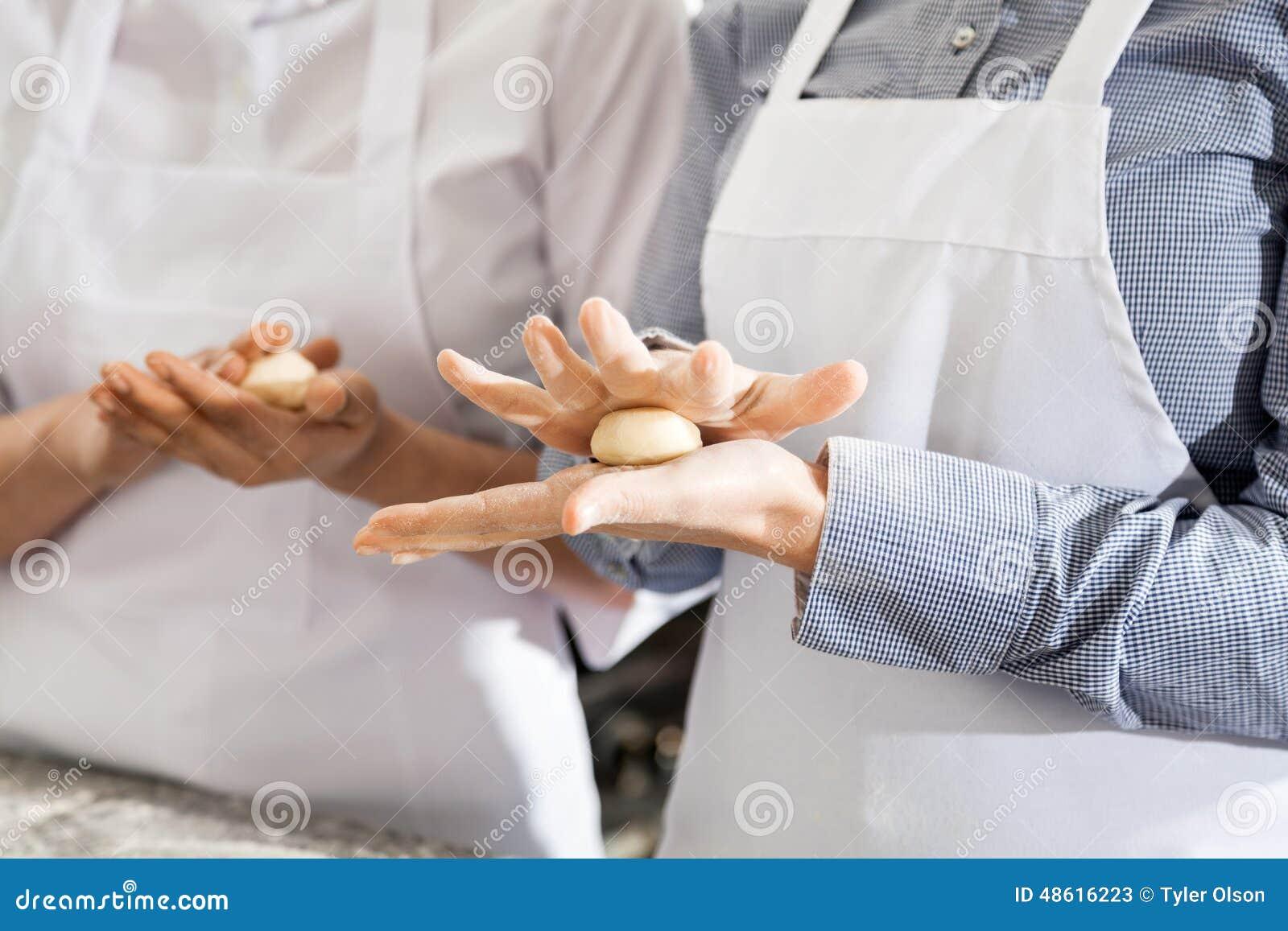 Θηλυκοί αρχιμάγειρες που κάνουν τις σφαίρες ζύμης ζυμαρικών στην κουζίνα