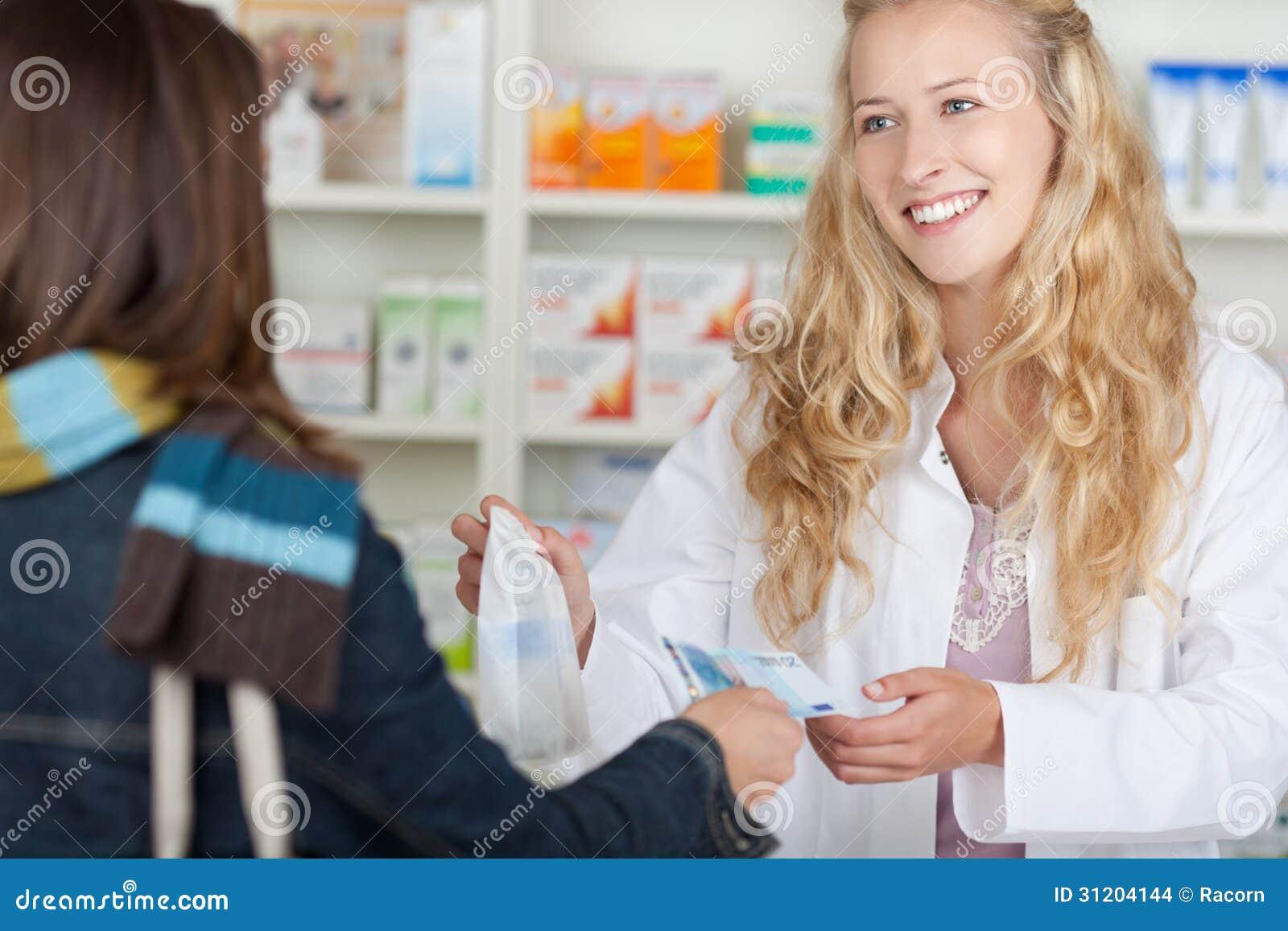 Θηλυκός φαρμακοποιός που λαμβάνει τα χρήματα από τον πελάτη για τα φάρμακα