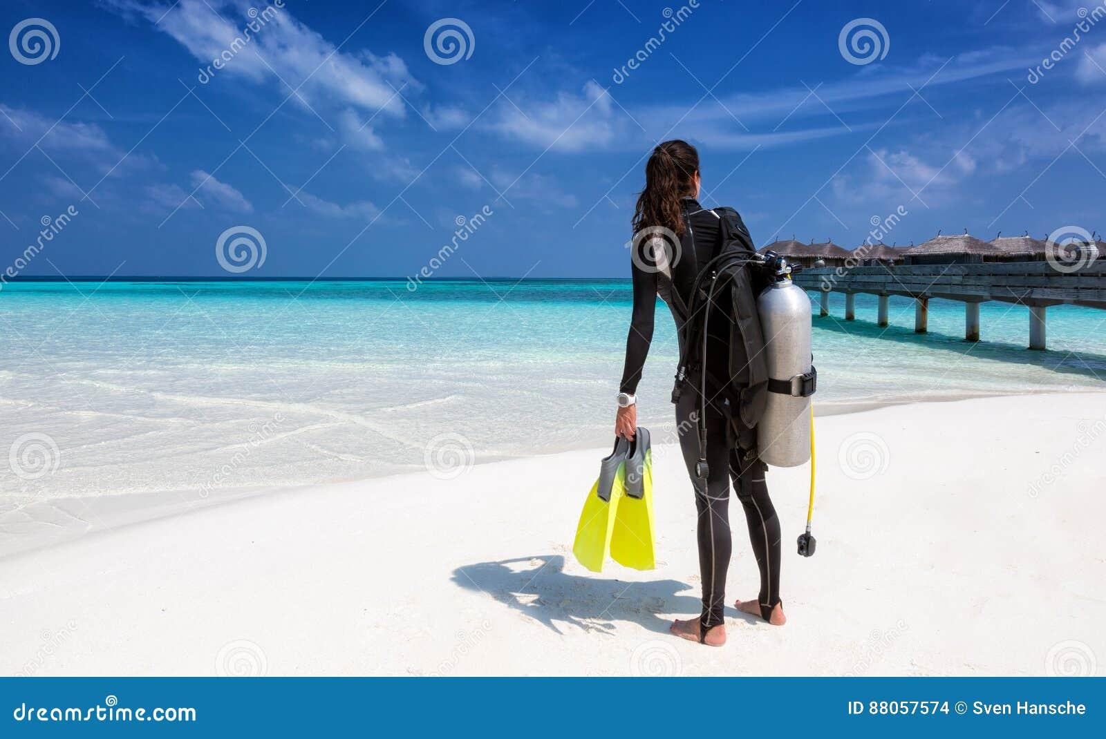 Θηλυκός δύτης σκαφάνδρων με τον εξοπλισμό κατάδυσης στην παραλία