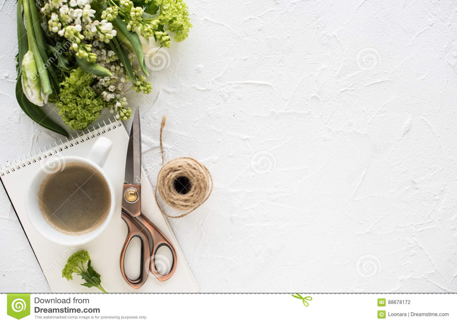 Θηλυκός flatlay με τα λουλούδια και ccoffee άσπρο tabletop