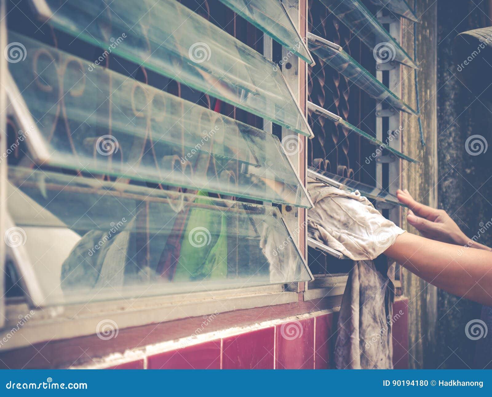 Θηλυκό τυφλό γυαλί παραθύρων χεριών καθαρίζοντας