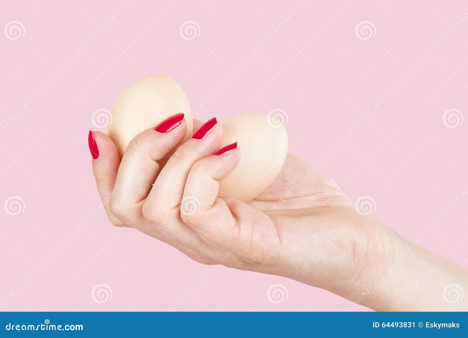 Θηλυκό χέρι με τα κόκκινα νύχια που κρατούν δύο αυγά