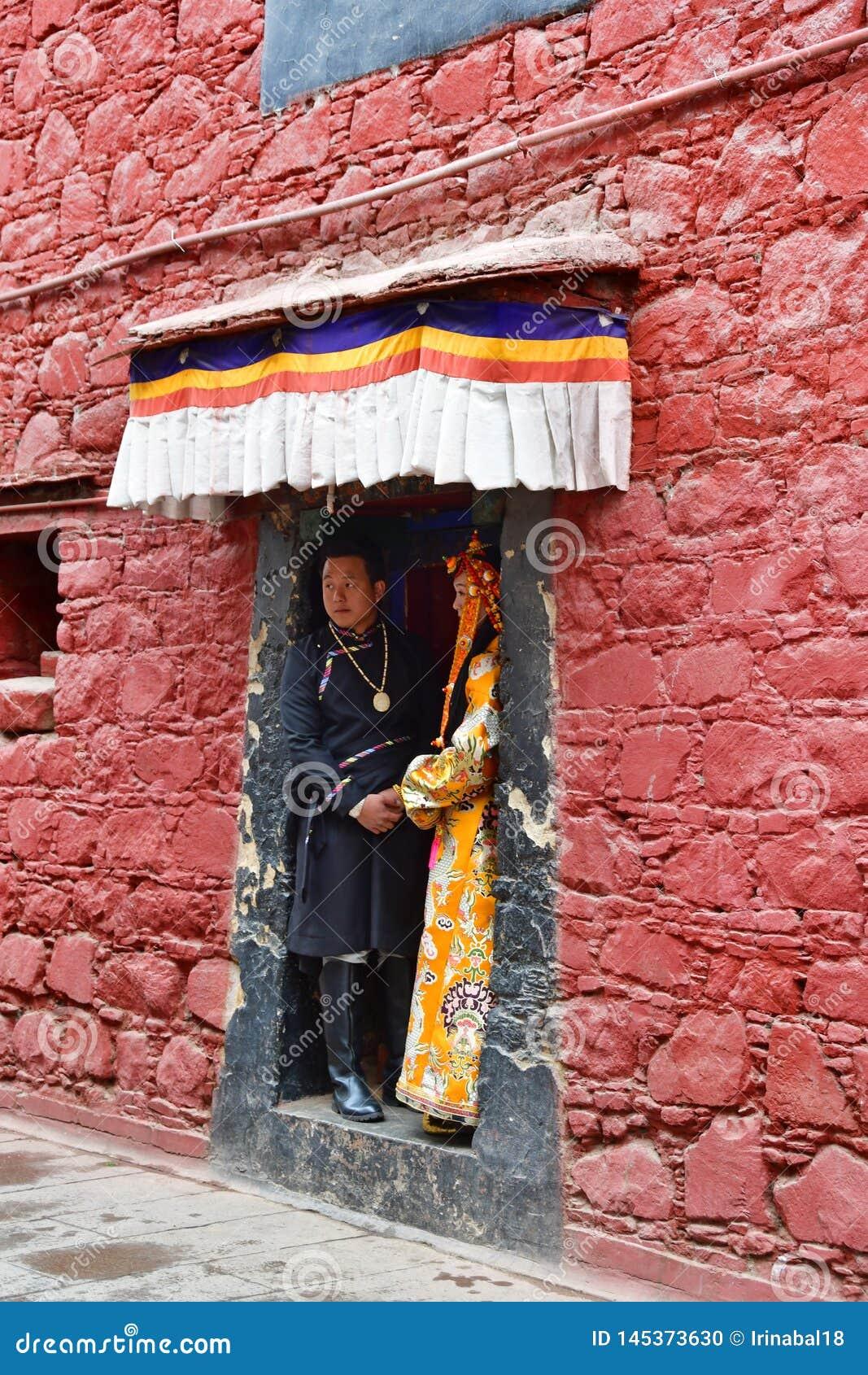 Θιβέτ, Lhasa, Κίνα, 03 Ιουνίου, 2018 Νέο ζεύγος των ανθρώπων στα εθνικά κοστούμια που στέκονται στην πόρτα του αρχαίου μοναστηριο