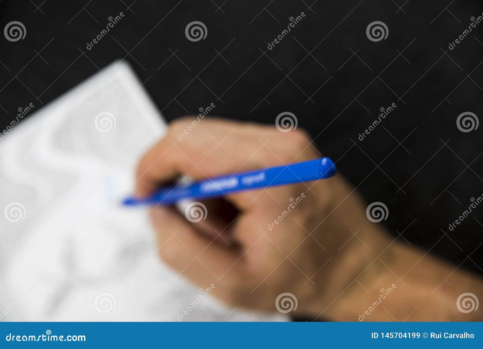 Θολωμένο χέρι που χειρίζεται έναν μπλε χρωματισμό μολυβιών