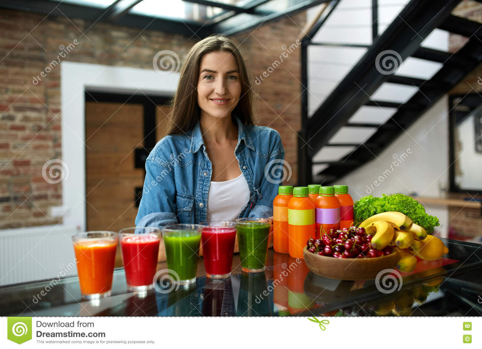 διατροφή σιτηρεσίου Γυναίκα με το φρέσκο καταφερτζή χυμού στην κουζίνα