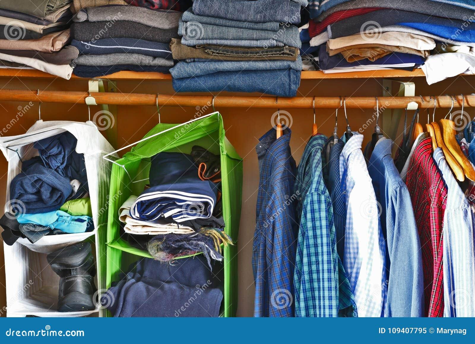 d95981dd6b7 Η ντουλάπα ατόμων με την ποικιλία των πουκάμισων που κρεμάστηκαν στις  κρεμάστρες και το σωρό του άλτη, των τζιν και των εσωρούχων βρέθηκε σε ένα  ράφι
