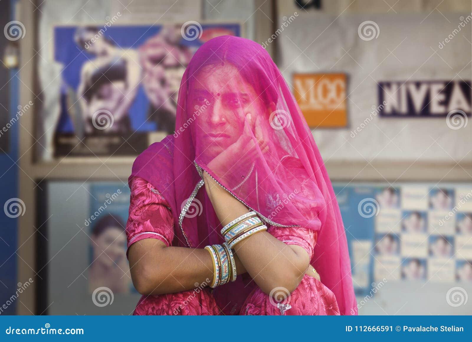 Ινδές γυναίκες που καλύπτονται από ένα ιώδες μαντίλι από ένα συντηρητικό fam μπροστά από ένα σύνολο πινάκων διαφημίσεων των εικόν