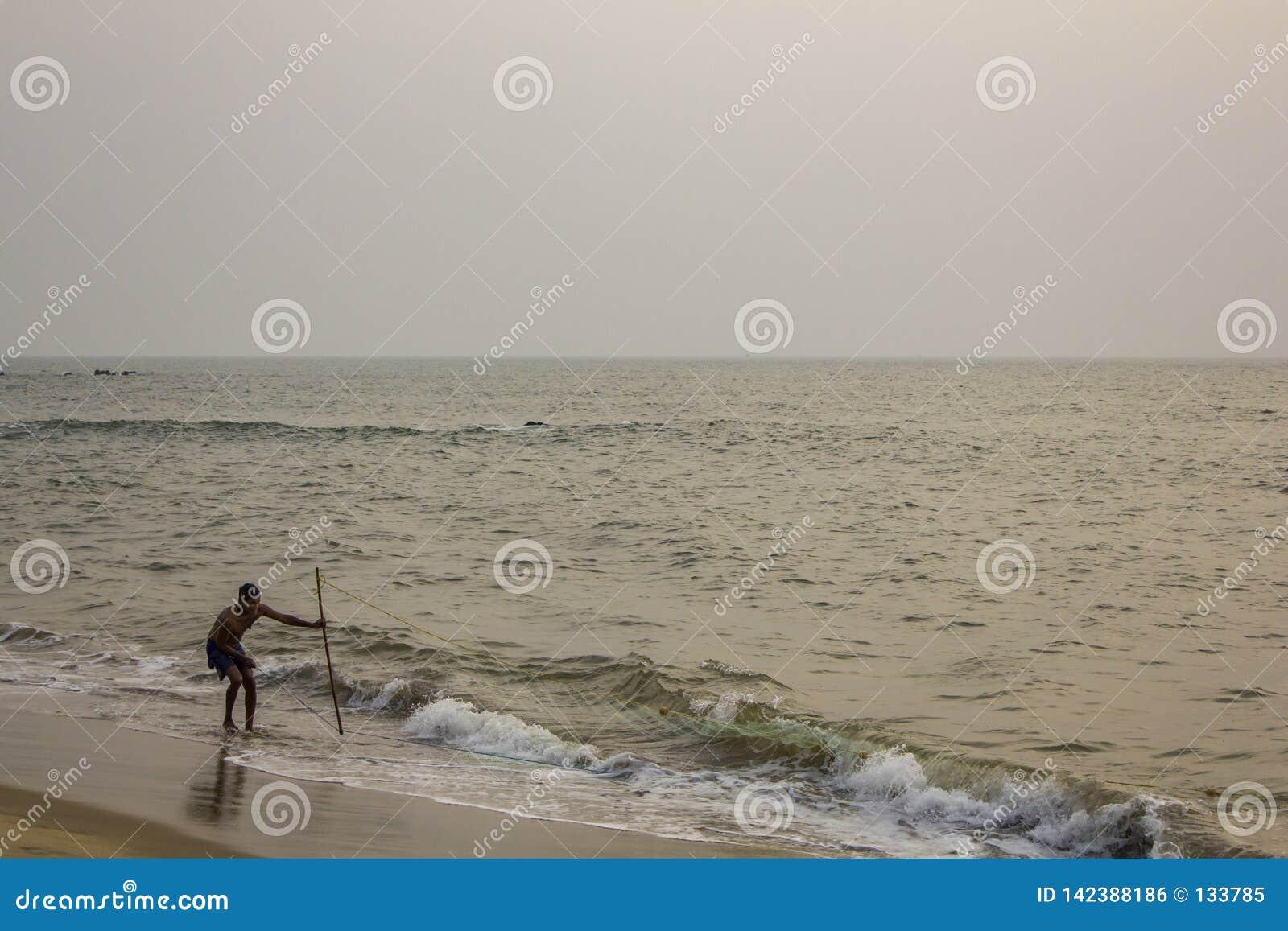 Ινδικός ψαράς με ένα δίχτυ του ψαρέματος σε μια αμμώδη παραλία ενάντια στον ωκεανό το βράδυ