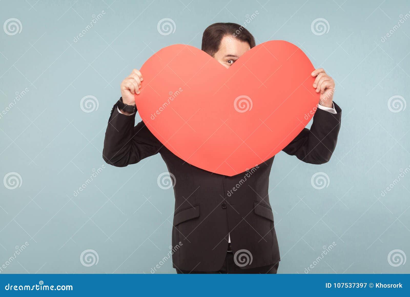 Ινκόγκνιτο αστείο άτομο που κρατά τη μεγάλη καρδιά και που φαίνεται ένα μάτι
