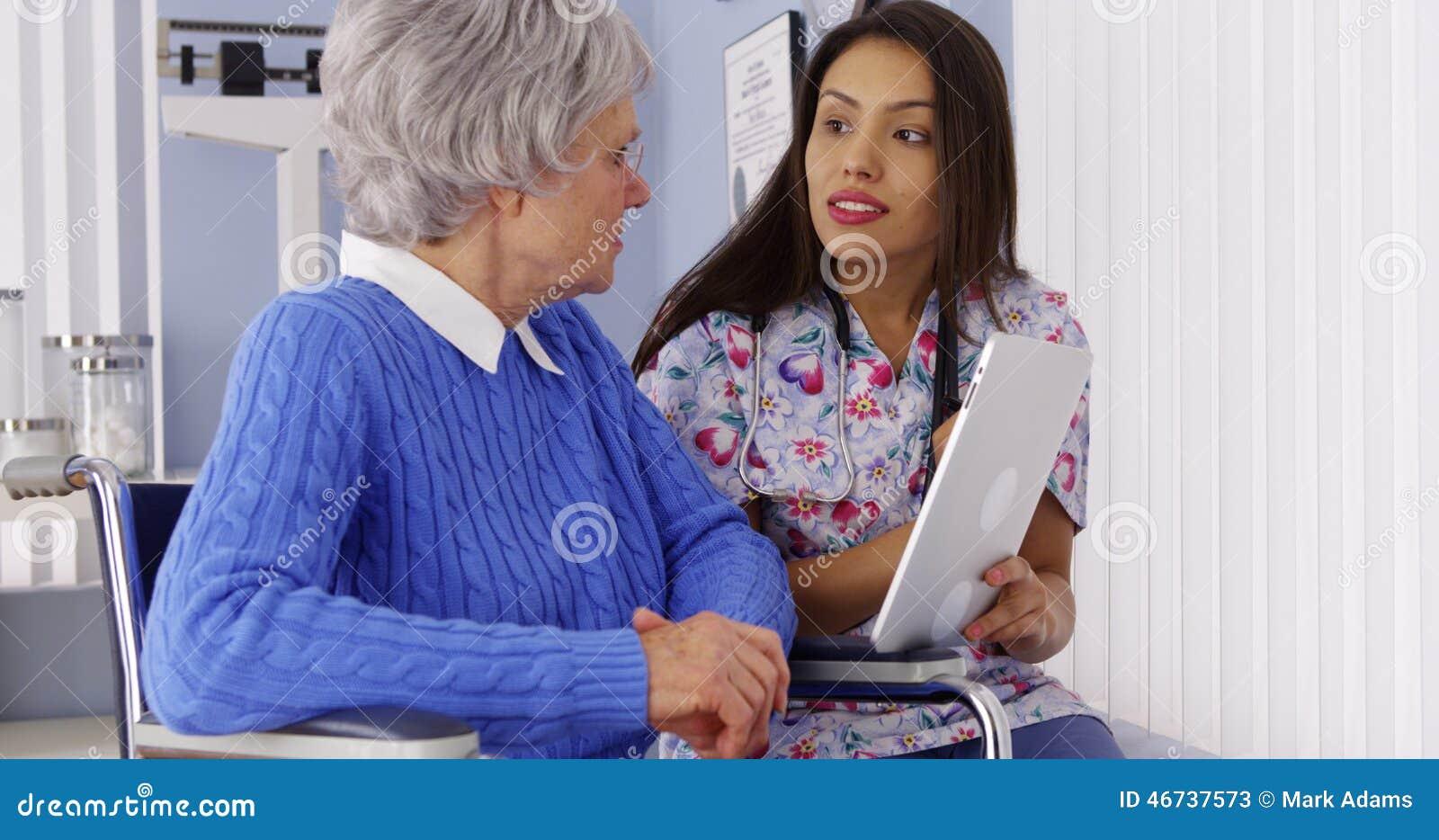 Ισπανικό caregiver που μιλά με την ταμπλέτα με τον ηλικιωμένο ασθενή
