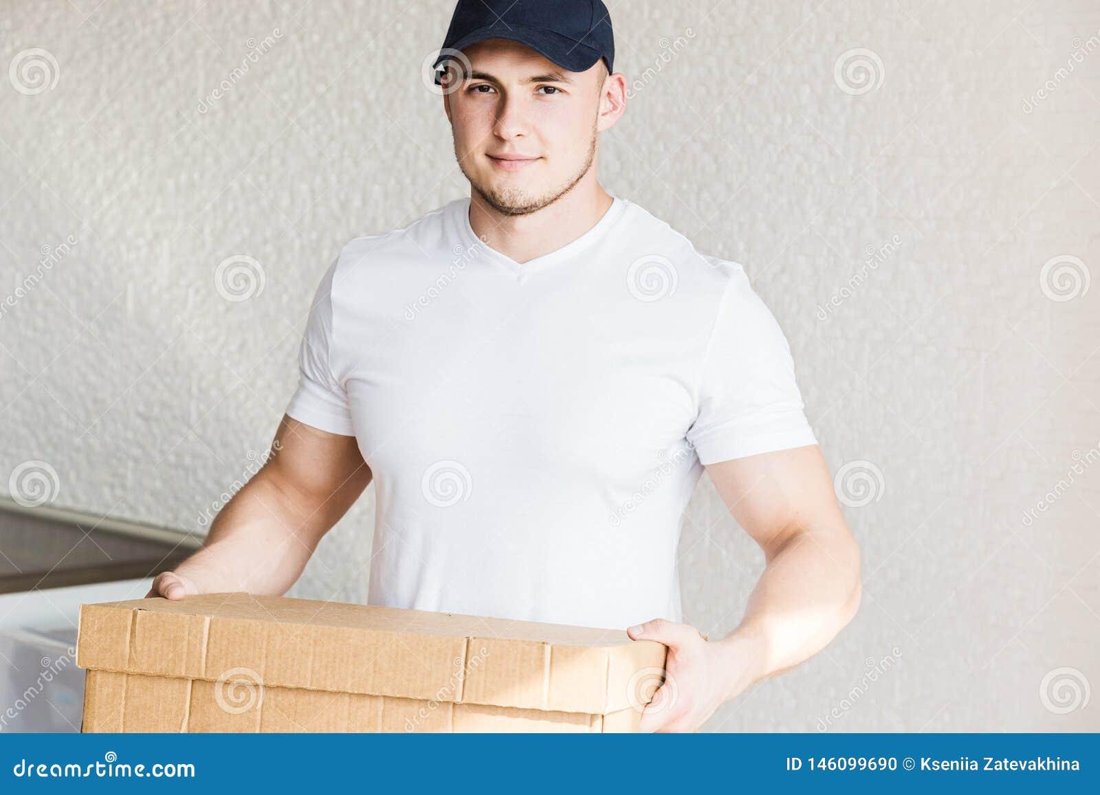 Ισχυρά, μυϊκά κουτιά από χαρτόνι φόρτωσης ατόμων παράδοσης για την κίνηση προς ένα διαμέρισμα επαγγελματικός εργαζόμενος της μετα