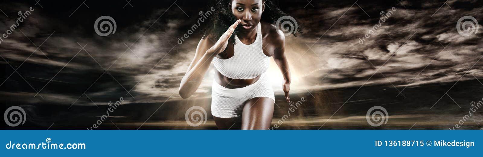Ισχυρή αθλητική γυναίκα sprinter, τρέχοντας στο σκοτεινό υπόβαθρο που φορά sportswear Ικανότητα και αθλητικό κίνητρο δρομέας
