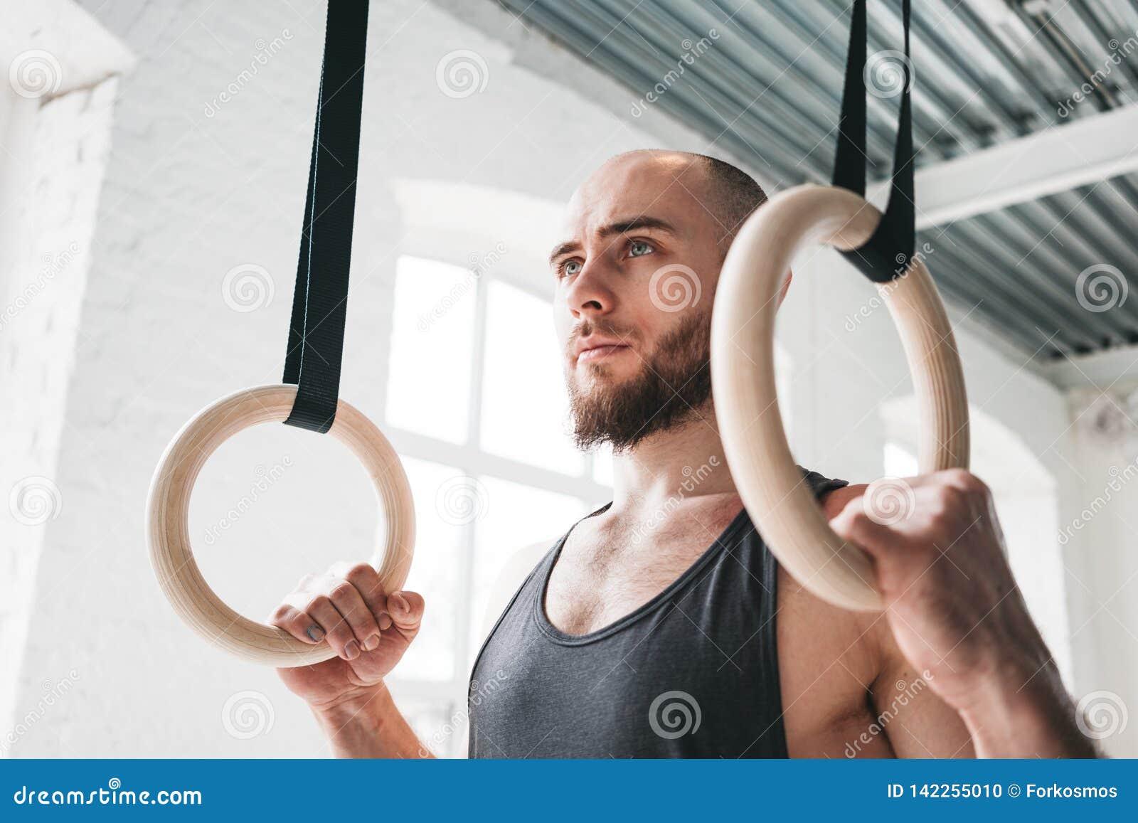 Ισχυρό γενειοφόρο άτομο που κρατά τα γυμναστικά δαχτυλίδια στη γυμναστική