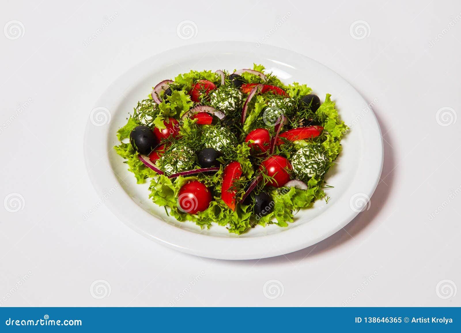 Ιταλική σαλάτα σφαιρών τυριών με τις ντομάτες και τα φρέσκα λαχανικά στο πιάτο