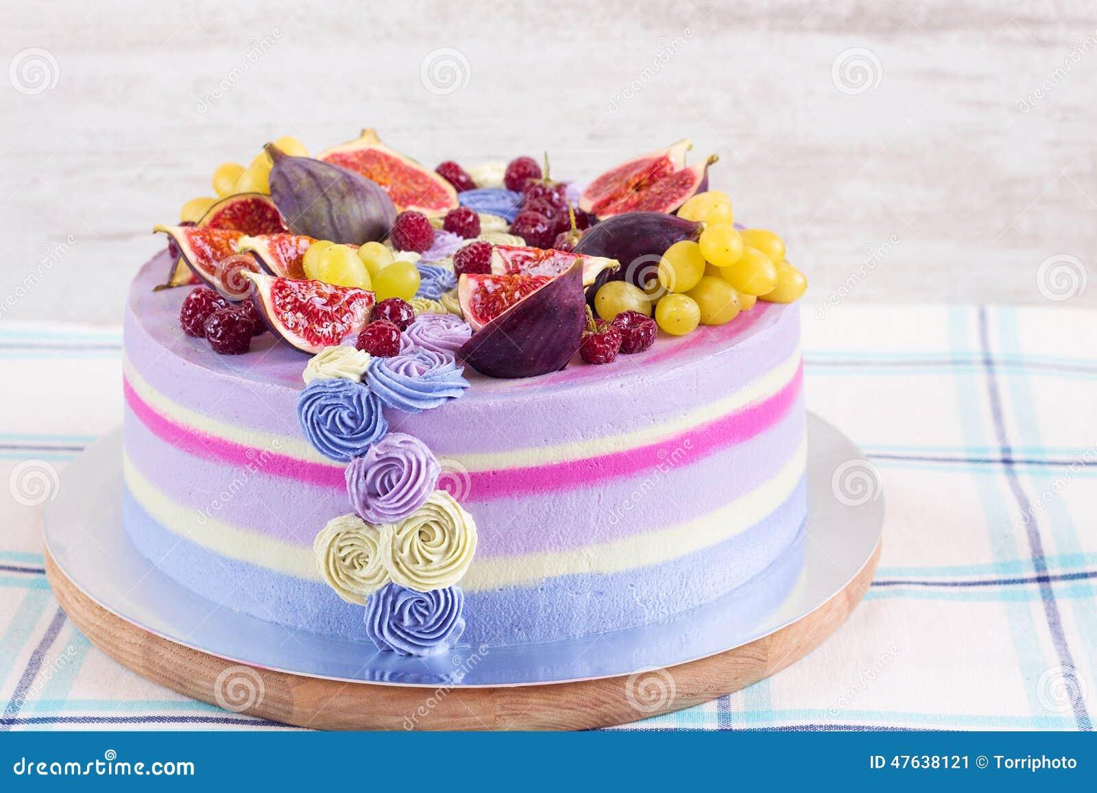 Ιώδες και ρόδινο κέικ με τα φρούτα στο άσπρο ξύλινο υπόβαθρο